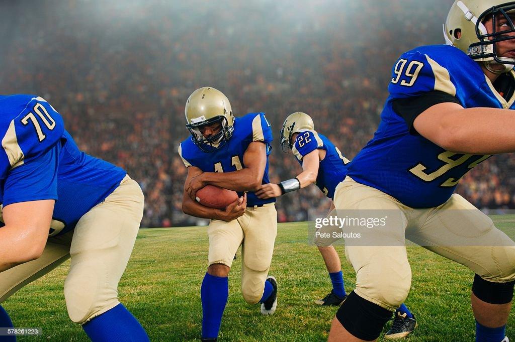 Team of teenage American football players playing on stadium pitch : Stock Photo