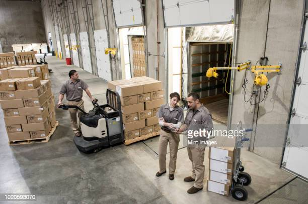 a team of three mixed race uniformed warehouse workers loading boxed products into the back of a truck in a distribution warehouse. - loading dock stock pictures, royalty-free photos & images