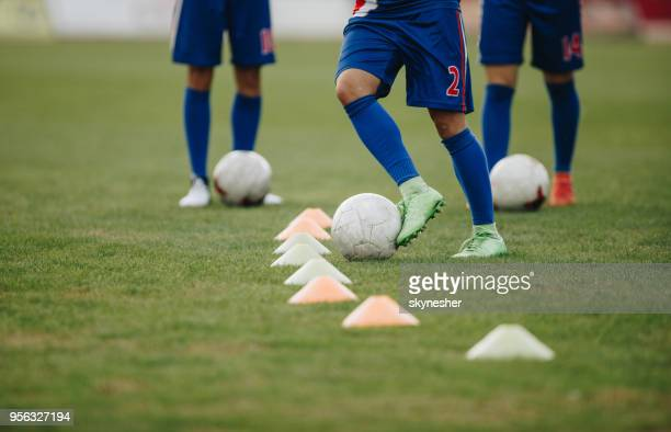 Team of unrecognizable soccer players practicing dribbling with balls on a playing field.