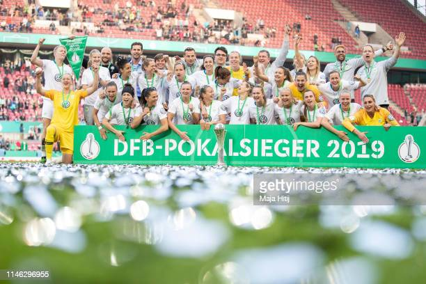 Team of VfL Wolfsburg celebrates with a trophy during medal ceremony after winning the Women's DFB Cup final match between VfL Wolfsburg and SC...