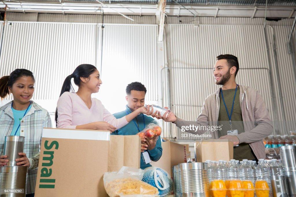 Team of volunteers sorts goods at food bank : Stock Photo
