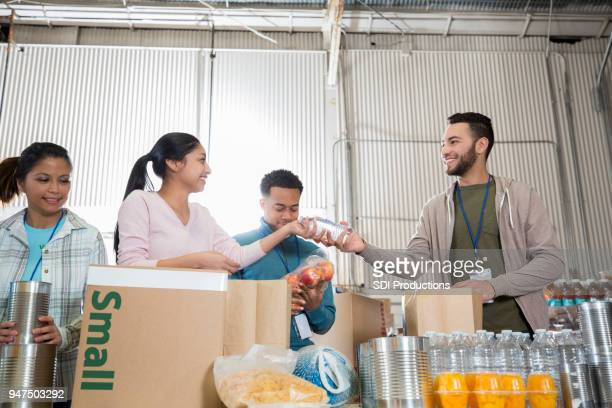 team of volunteers sorts goods at food bank - humanitarian aid stock pictures, royalty-free photos & images
