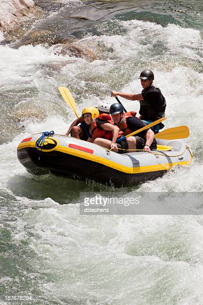 Team of Whitewater Rafters Going Down a River