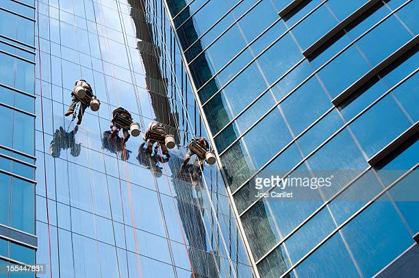 window washer team cleaning high rise exterior - window cleaning stock photos and pictures