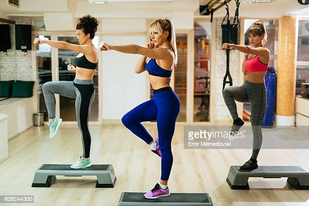 Team of women exercising step aerobics at the gym.