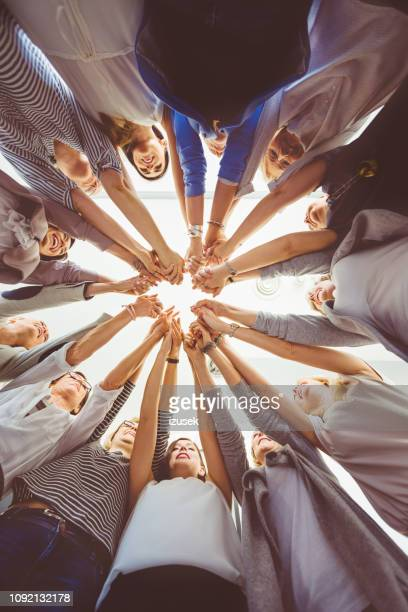 team of women holding hands - vertical stock pictures, royalty-free photos & images