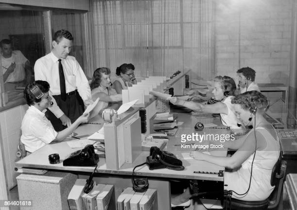 A team of women seated wearing headsets are pictured answering telephone calls as a man standing is shown some paperwork