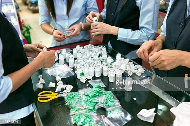 A team of workers repackage medicine in a pharmacy