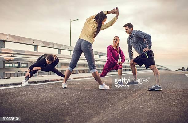 Équipe de jeunes joueurs de faire des exercices de détente sur une route.