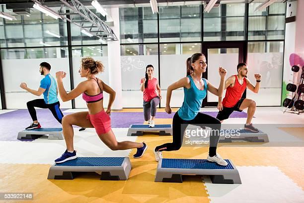 Equipe de jovens atletas ter Aeróbica passo treino no ginásio.
