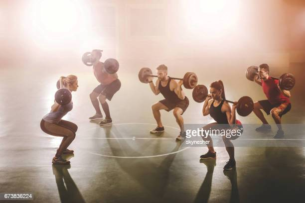 team of young athletes weightlifting in a health club. - circuit training stock photos and pictures