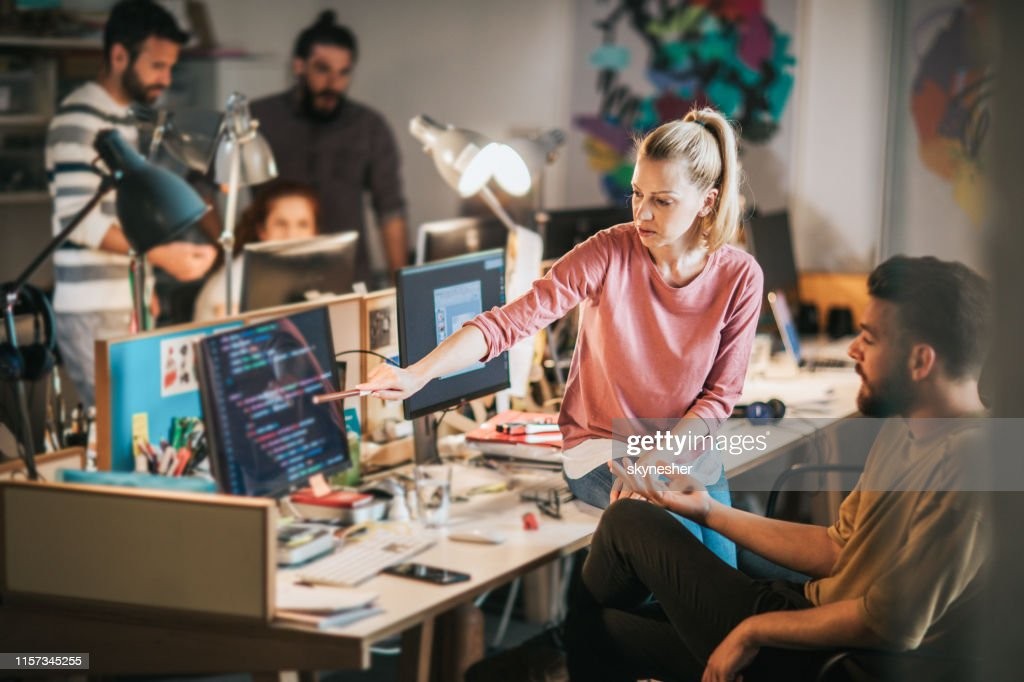 Team of young computer programmers cooperating in the office. : Stock Photo