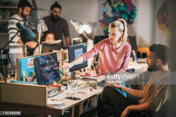 team of young computer programmers cooperating in the office. - millennial generation stock pictures, royalty-free photos & images