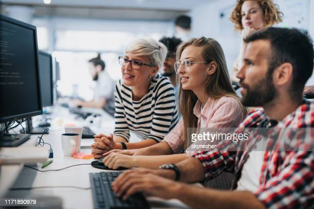 team of young computer programmers cooperating while working on desktop pc in the office. - it support stock pictures, royalty-free photos & images