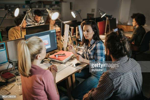 team of young computer programmers talking in the office. - graphic designer stock pictures, royalty-free photos & images