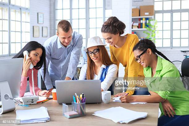 Team of young coworkers discussing ideas in modern office
