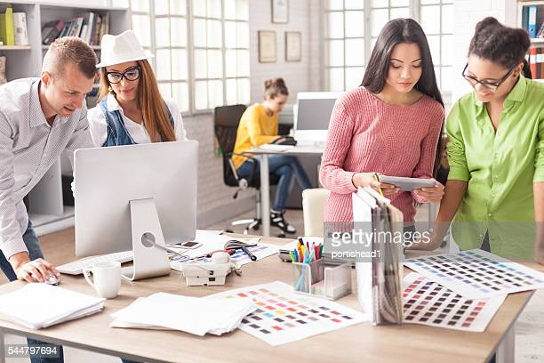 Team of young creative designers working at modern workplace