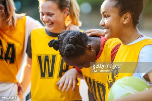 team of young netball players laughing with arms around each other on outdoors netball court