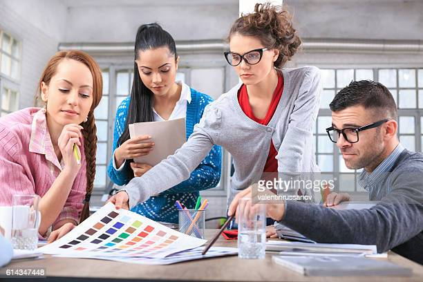 Team of young people discussing color schemes at studio