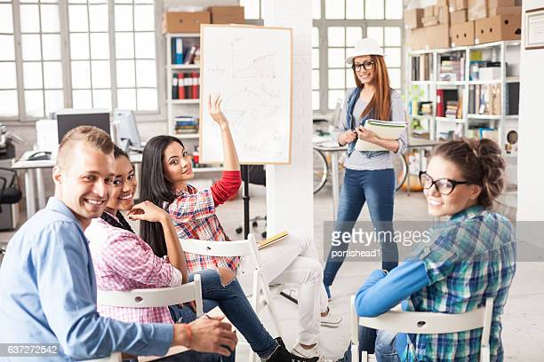 Team of young people making presentation in workplace