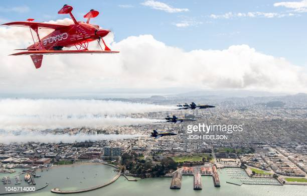TOPSHOT Team Oracle aerobatics pilot Sean D Tucker flies above the US Navy Blue Angels over San Francisco California as part of a practice run for...