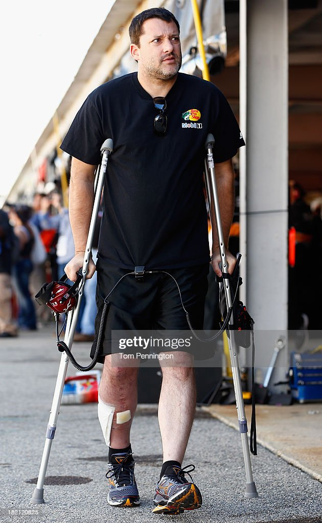 Team owner and injured driver Tony Stewart walks through the garage area on crutches during practice for the NASCAR Sprint Cup Series AAA 400 at Dover International Speedway on September 28, 2013 in Dover, Delaware.