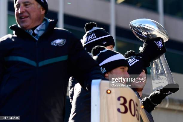 Team owner Jeffrey Lurie with quarterbacks Nick Foles Nate Sudfeld and Carson Wentz of the Philadelphia Eagles acknowledge fans as Sudfeld hoists the...
