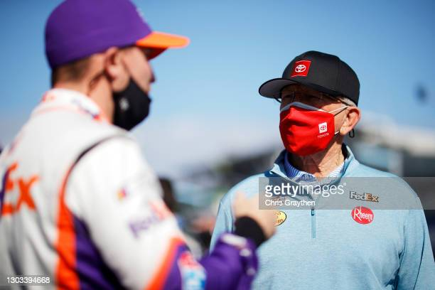 Team owner Joe Gibbs and Denny Hamlin, driver of the FedEx Express Toyota, talk on the grid prior to the NASCAR Cup Series O'Reilly Auto Parts 253 at...