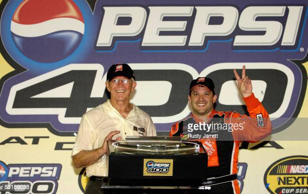 Team owner Joe Gibbs and Tony Stewart driver of the Home Depot Chevrolet celebrate winning the NASCAR Nextel Cup Series Pepsi 400 on July 2 2005 at...