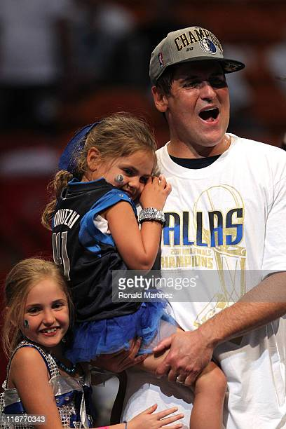 Team owner Mark Cuban of the Dallas Mavericks celebrates with his daughters Alexis Sofia and Alyssa after the Mavericks won 10595 against the Miami...