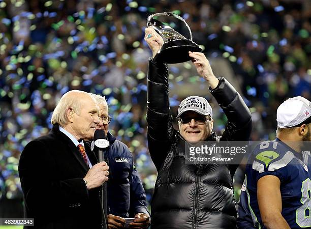 Team owner Paul Allen of the Seattle Seahawks holds up the George Halas Trophy after the Seahawks defeat the San Francisco 49ers 2317 during the 2014...