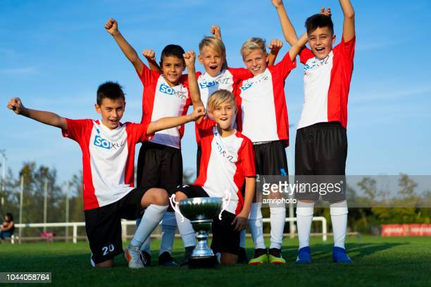 team photo successful junior soccer team 10 years old boys celebrating first place - 10 11 years stock pictures, royalty-free photos & images