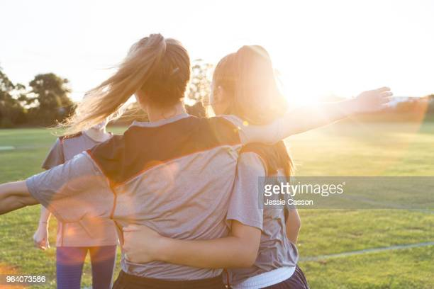 team players embrace on the sports field in the evening light - sport di squadra foto e immagini stock
