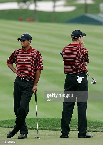 Team players Tiger Woods and Jim Furyk wait to putt during their foursome match at the Presidents Cup golf tournament in Gainesville, Virginia,...