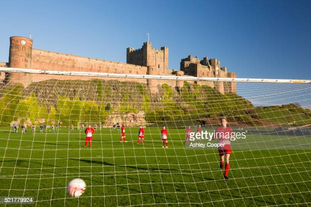 A team playing football infront of Bamburgh Castle, Northumberland, UK.