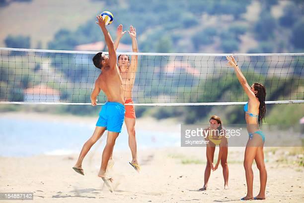 Team plays beach volleyball.