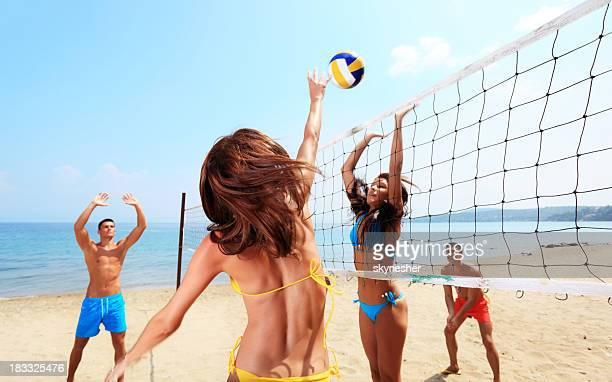 Team plays beach volleyball.