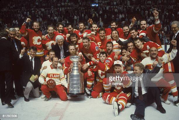 Team portrait of the players and staff of the Calgary Flames as they pose on the ice with the Stanley Cup trophy after they defeated the Montreal...