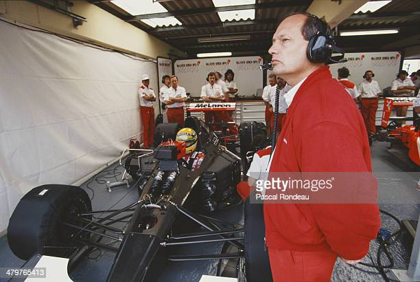Team principle Ron Dennis looks on as Ayrton Senna sits aboard the Honda Marlboro McLaren McLaren MP4/6 Honda RA121E V12 during practice for the...