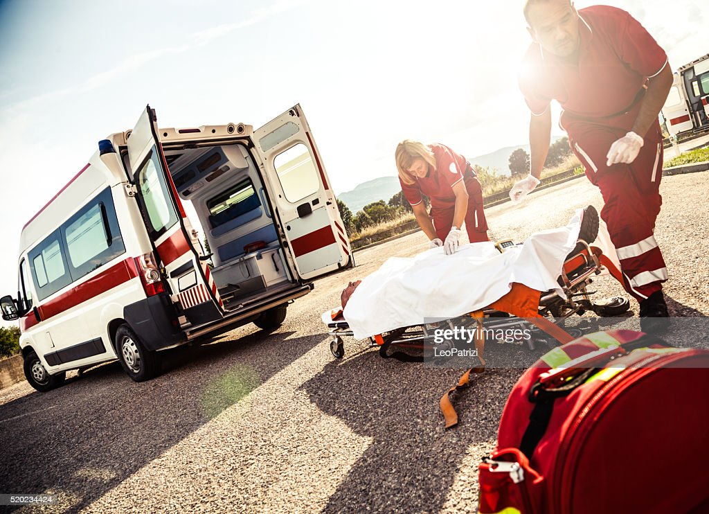 EMT team provide first aid on the street : Stock Photo