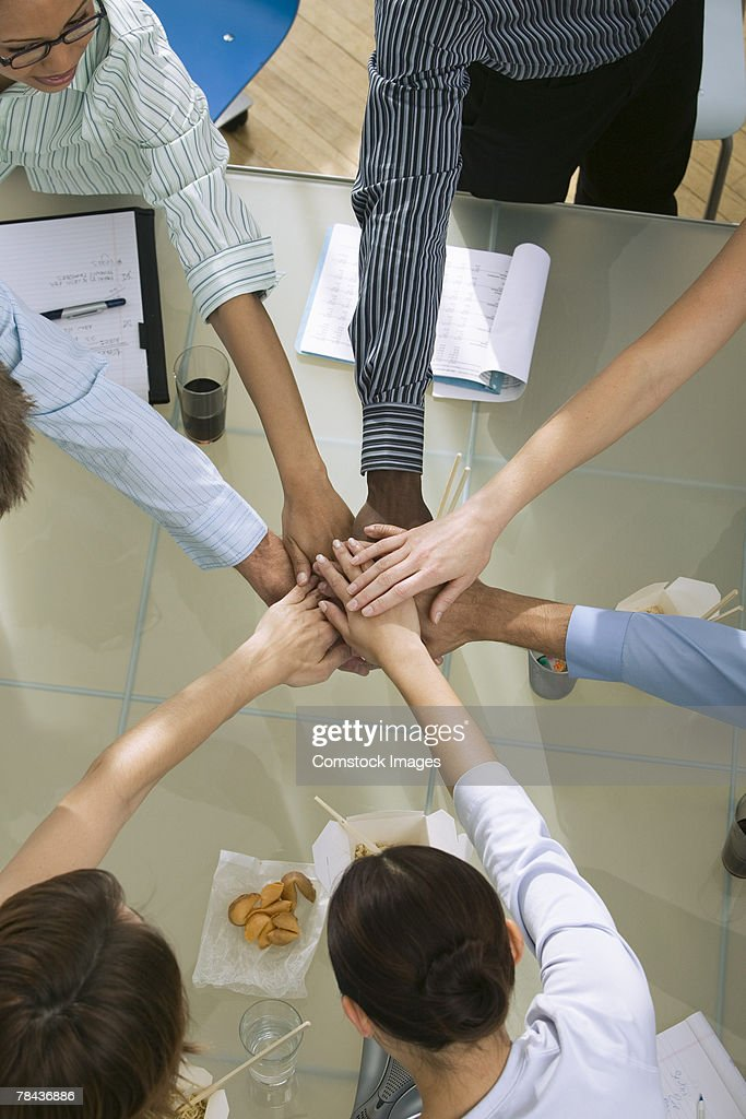 Team putting hands together : Stockfoto