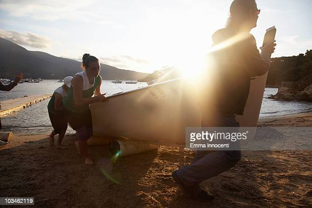 team putting rowboat on shore