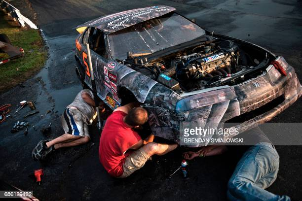 TOPSHOT A team repairs a car before a race at Ace Speedway in Alamance County May 19 2017 in Altamahaw North Carolina / AFP PHOTO / Brendan Smialowski