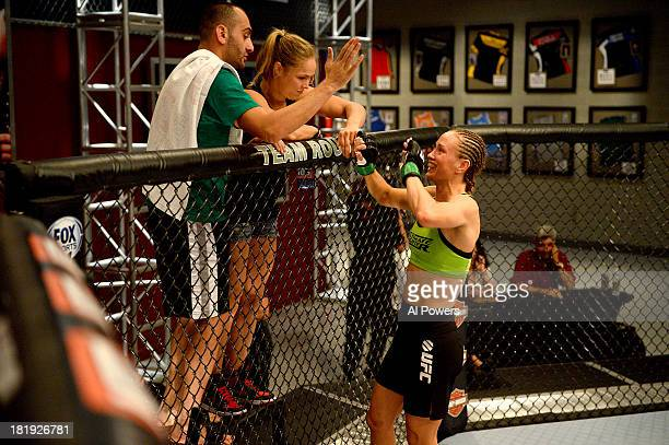 Team Rousey trainer Edmond Tarverdyan and Coach Ronda Rousey speak to Jessica Rakoczy in her corner before her bout against Roxanne Modafferi in...