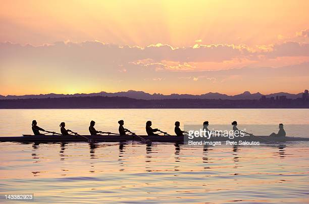 team rowing boat in bay - rowing stock pictures, royalty-free photos & images