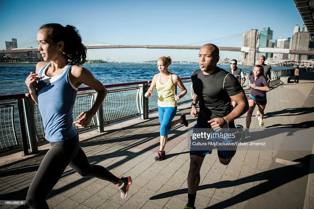 Team running together on waterfront, New York, USA : Stock Photo