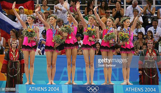 Team Russia stand waving on the podium after receiving the gold medal in the rhythmic gymnastics group category on August 28 2004 during the Athens...