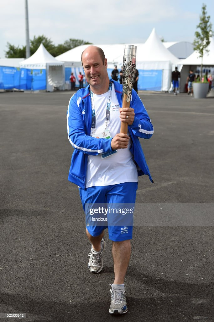 Team Scotland chef de mission Jon Doig carries the Glasgow 2014 Queen's Baton through the Commonwealth Games Athletes' Village on July 23, 2014 in Glasgow, Scotland. Scotland is nation 70 of 70 nations and territories the Queen's Baton will visit.