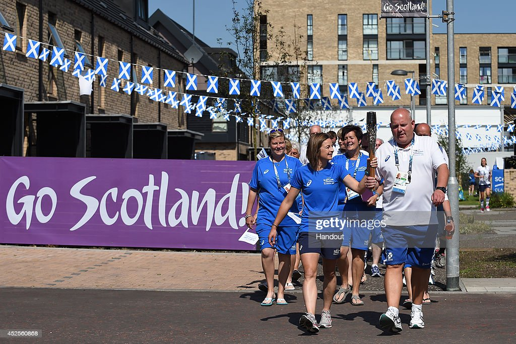 Team Scotland's hockey player Linda Clement and lawn bowler Alex Marshall carry the Glasgow 2014 Queen's Baton through the Team Scotland camp at the Commonwealth Games Athletes' Village on July 23, 2014 in Glasgow, Scotland. Scotland is nation 70 of 70 nations and territories the Queen's Baton will visit.
