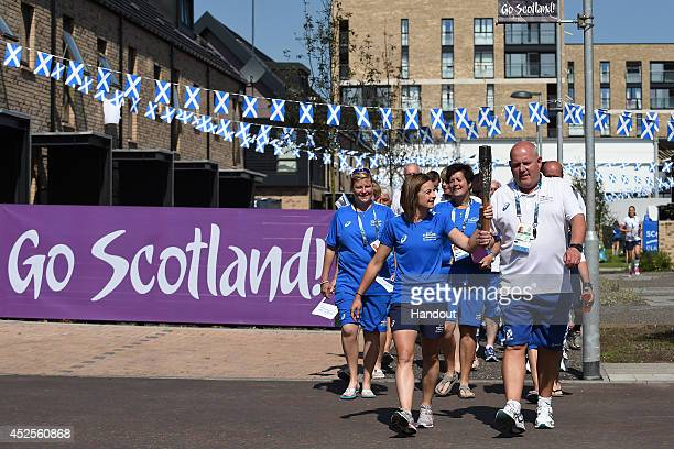 Team Scotland's hockey player Linda Clement and lawn bowler Alex Marshall carry the Glasgow 2014 Queen's Baton through the Team Scotland camp at the...